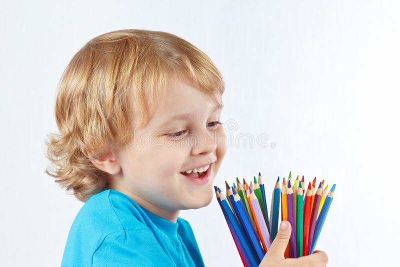 Kleines nettes Kind mit Farbe zeichnet auf weißem Hintergrund an stockfotografie