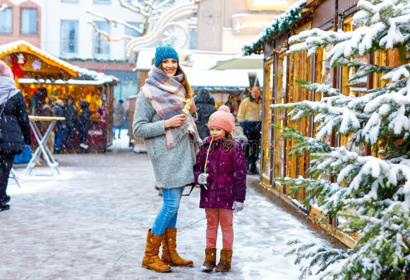 Kleines nettes Kindermädchen und junge Mutter, die Spaß auf traditionellem deutschem Weihnachtsmarkt während der starken Schneefä lizenzfreie stockbilder