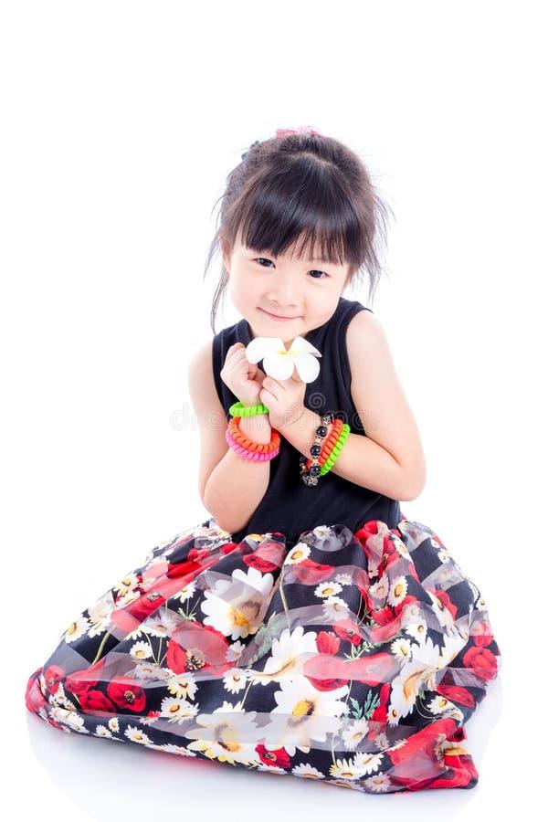 Kleines nettes Mädchen, das auf dem Boden über Weiß sitzt stockfotos