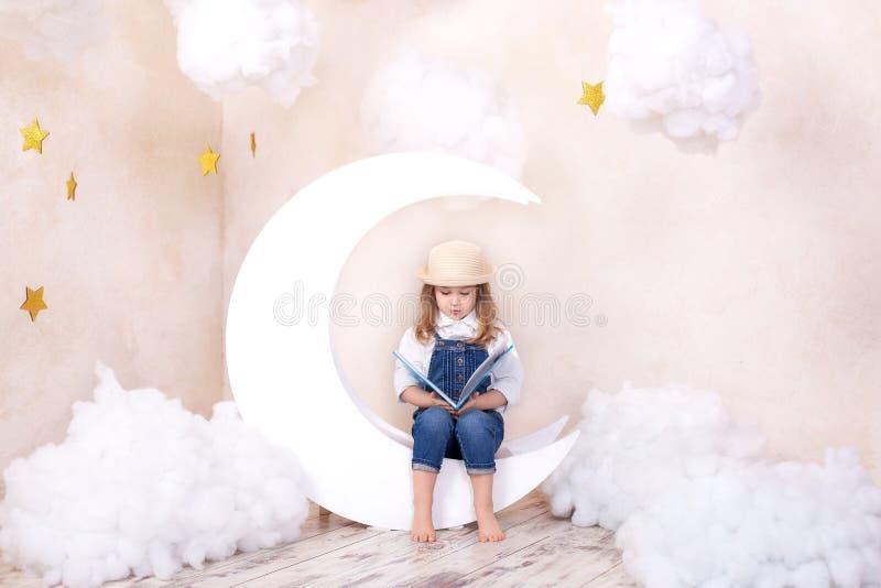Kleines nettes Mädchen, das auf dem Mond mit Wolken und Sternen mit einem Buch in ihren Händen und in Ablesen sitzt Das M?dchen l stockfotografie