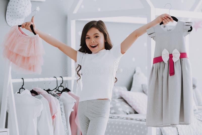 Kleines nettes Mädchen, das ein Kleid im Schlafzimmer wählt stockfoto