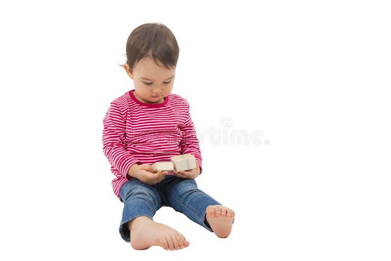Kleines nettes Mädchen, das eine Geschenkbox, lokalisiert auf dem Weiß öffnet stockfotografie