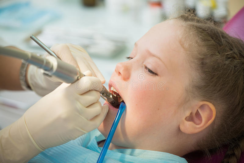 Kleines nettes Mädchen, das im Stuhl an der Zahnarztklinik während der zahnmedizinischen Überprüfung und der Behandlung, Nahaufna lizenzfreies stockfoto