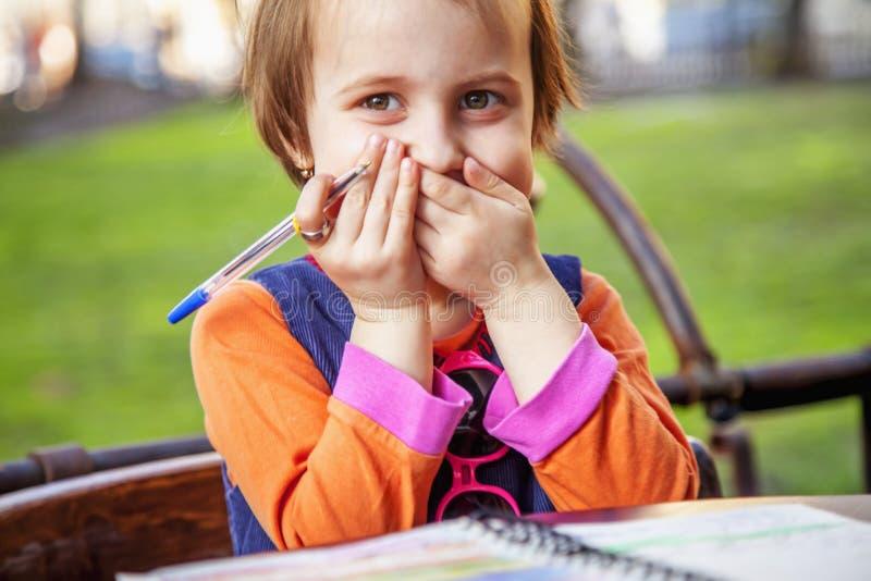 Kleines nettes Mädchen des lustigen Porträts Kinder, daseinen Brief lacht und schreibt Positives Gefühl, Ausbildung und glücklich lizenzfreies stockbild