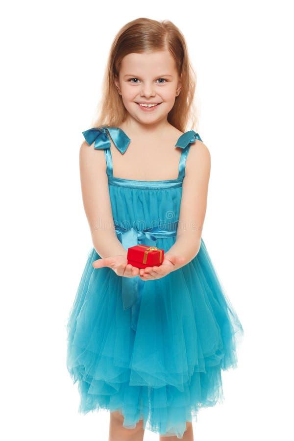 Kleines nettes Mädchen im blauen Kleid, das eine Geschenkbox, lokalisiert auf dem weißen Hintergrund hält lizenzfreie stockbilder