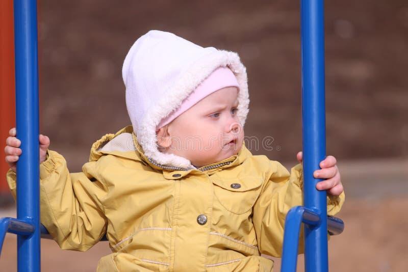 Kleines nettes Mädchen im Schwingen der gelben Jacke lizenzfreie stockbilder