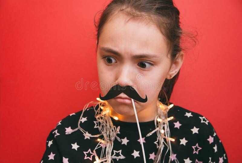 Kleines nettes Mädchen mit einer Girlande um ihren Hals, der Stützen eines Schnurrbartes auf einem roten Hintergrund hält lizenzfreie stockbilder