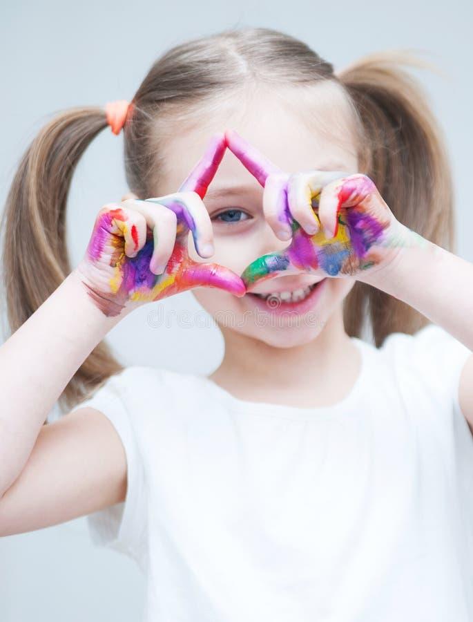 Kleines nettes Mädchen mit gemalte Hände lizenzfreie stockfotografie