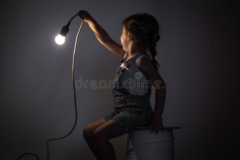 Kleines nettes Mädchen mit Glühlampe in der Hand stockbild