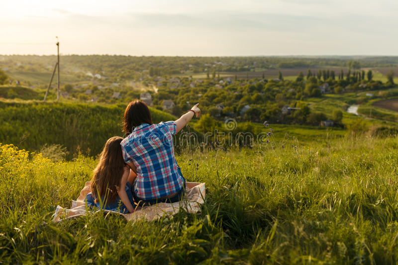 Kleines nettes Mädchen mit ihrer Mutter, die bei Sonnenuntergang sitzt lizenzfreies stockfoto