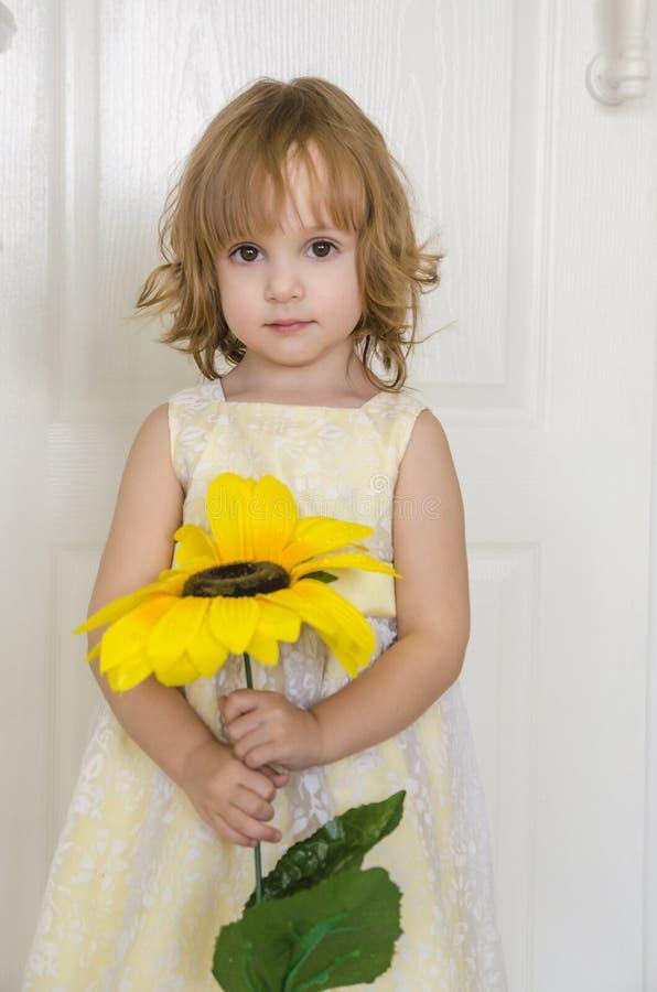 Kleines nettes Mädchen mit Uhren einer Sonnenblume auf der Blume stockfotografie