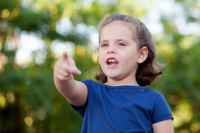 Kleines nettes Mädchen, welches die Richtung anzeigt stockfotografie