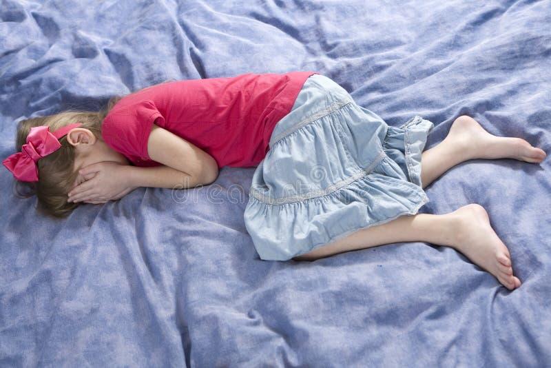 Kleines nettes Mädchenabschlußgesicht durch Hände. lizenzfreies stockbild