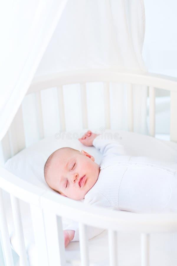 Kleines neugeborenes Baby, das in der weißen runden Krippe schläft stockfotos