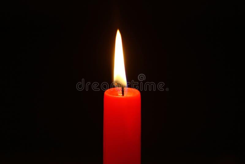 Kleines Paraffin, das rote Kerze mit hellem Feuer auf dem schwarzen Hintergrund brennt stockfotografie
