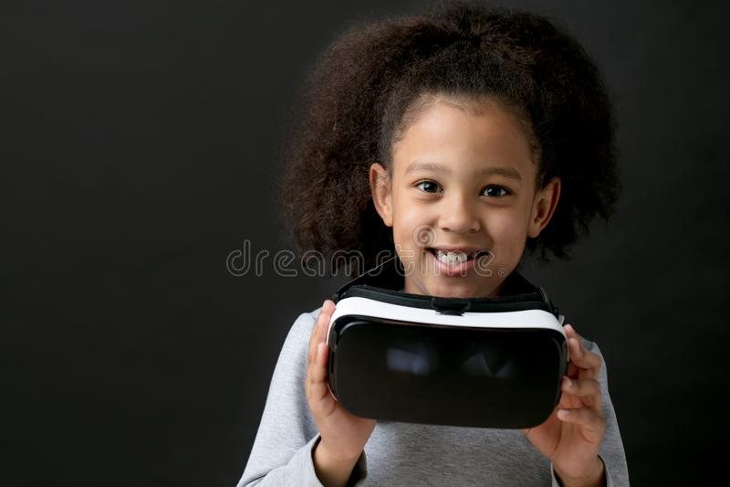 Kleines positives metis Mädchen, das VR-Gläser hält Getrennter schwarzer Hintergrund stockfotografie