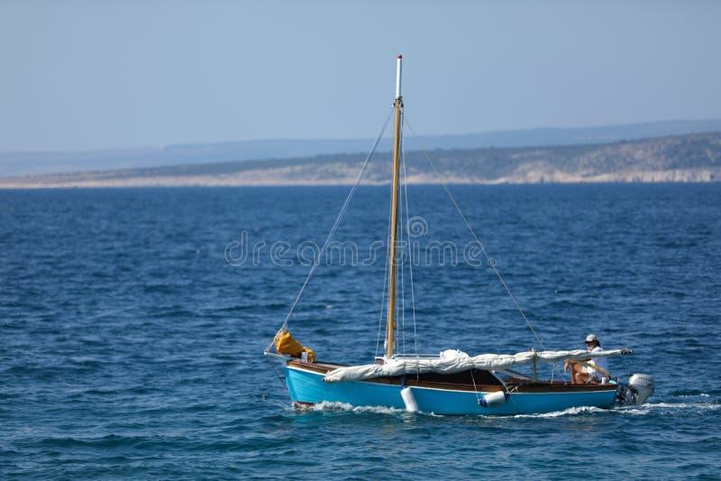 Kleines Produkteinführungsboot mit Leuten, blauem Meer und Himmel lizenzfreie stockfotos