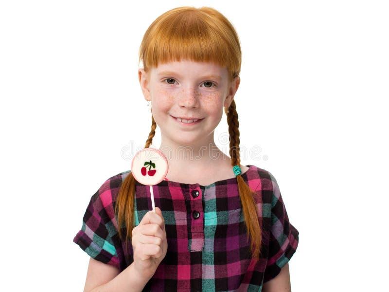 Kleines redheaded Mädchen, das eine Süßigkeit mit einer Kirsche hält stockfotos