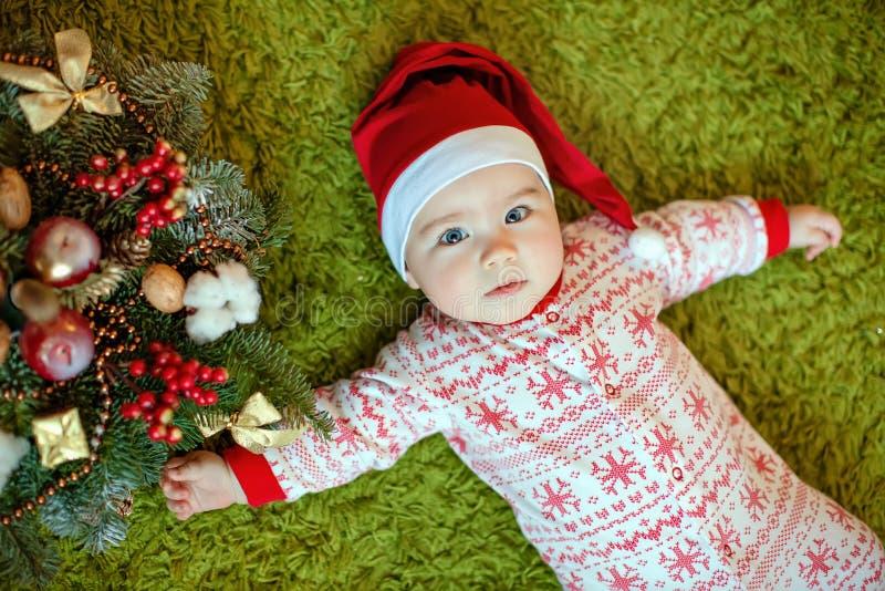 Kleines reizend Baby in roten Sankt-Hüten und -pyjamas mit snowf lizenzfreie stockfotos