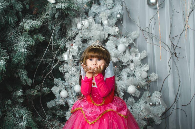 Kleines reizend weibliches Kind in einem rosa Kleiderschlagschnee in den Händen, Weihnachtsdekorationen lizenzfreie stockfotos