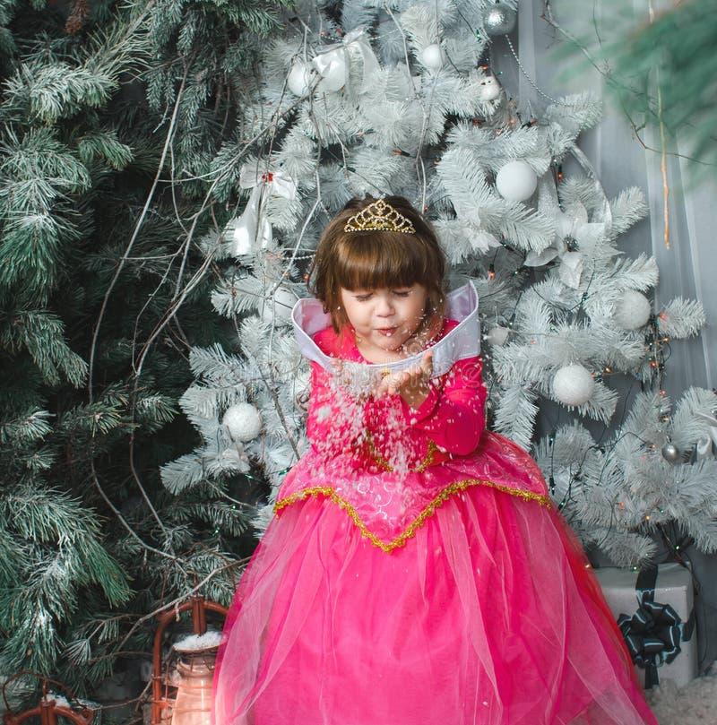 Kleines reizend weibliches Kind in einem rosa Kleiderschlagschnee in den Händen, Weihnachtsdekorationen stockfotos