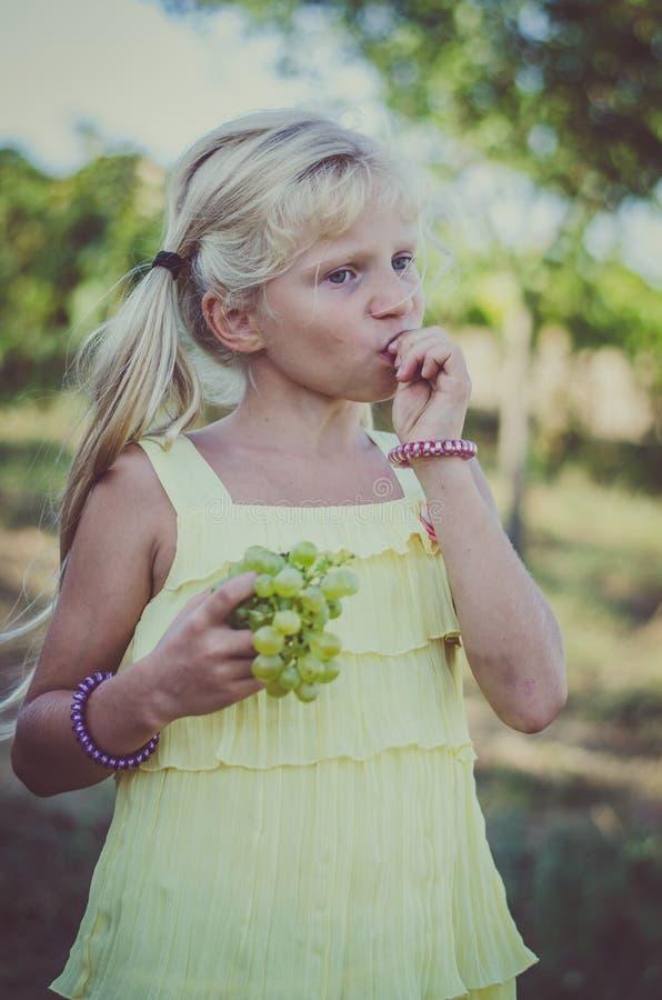 Kleines reizendes Mädchen im gelben Kleid Trauben essend lizenzfreie stockfotografie