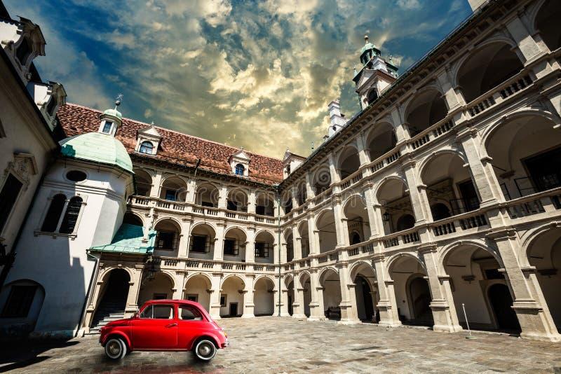 Kleines rotes Auto der alten Weinlese in der historischen Szene Altes Gebäude Klagenfurts stockfotografie