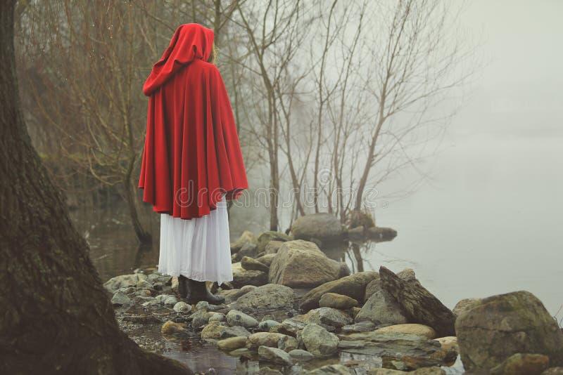 Kleines Rotkäppchen auf einem Ufer von einem nebelhaften See lizenzfreies stockfoto