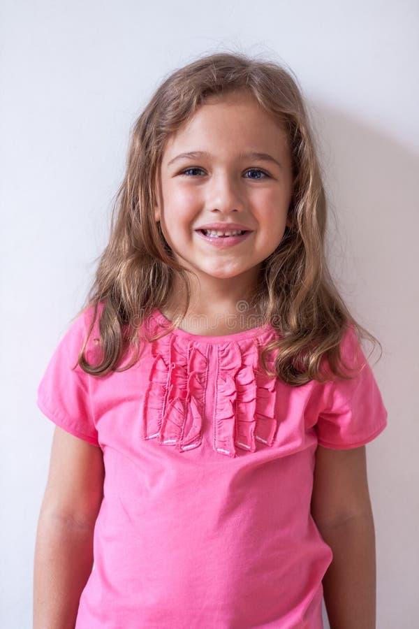 Kleines russisches Sechsjahresmädchen im rosa T-Shirt auf weißem Hintergrund lizenzfreie stockbilder