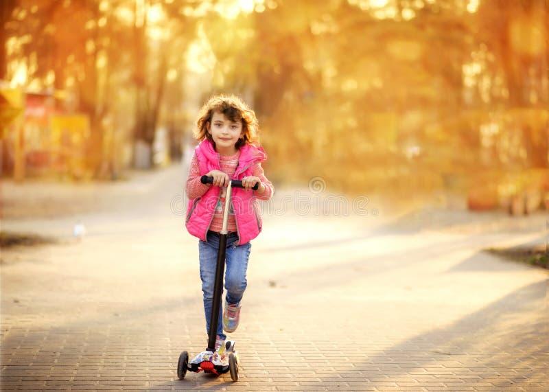 Kleines, süßes 6-jähriges Mädchen in Jeans und rosa Vest Reiten Scooter bei Sonnenuntergang im Park Kind mit aktivem Lebensstil K lizenzfreies stockbild