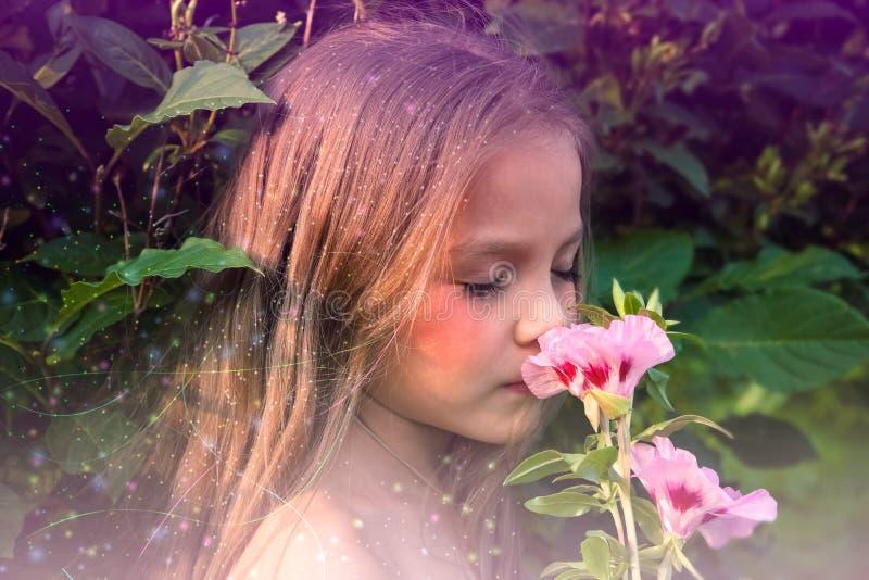 Kleines schönes Mädchen, das eine Blume riecht stockbild