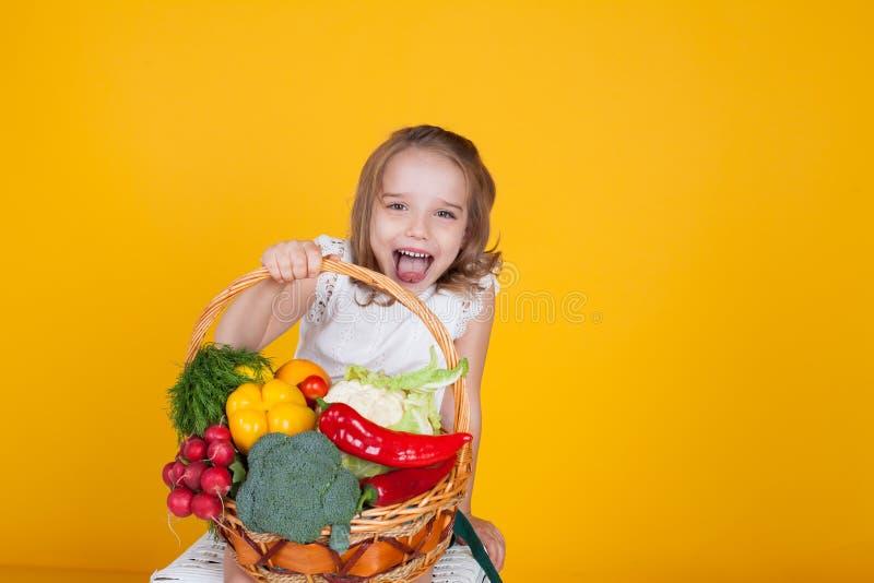 Kleines schönes Mädchen, das einen Korb des frischen Obst und Gemüse der gesunden Nahrung hält lizenzfreie stockbilder