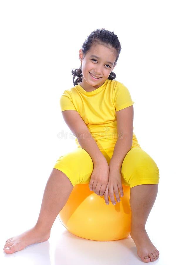 Kleines schönes Mädchen im Gelb mit gelber Kugel lizenzfreie stockfotografie