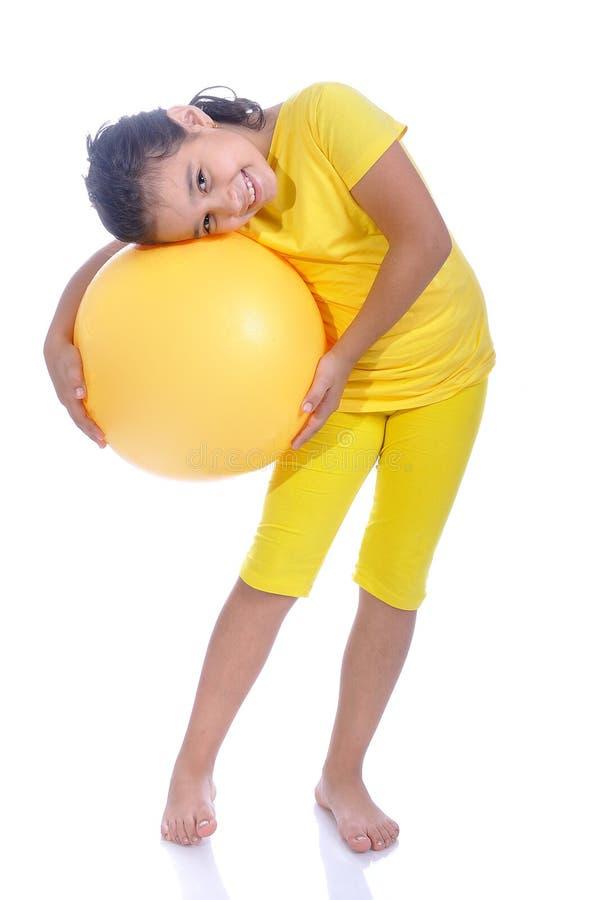 Kleines schönes Mädchen im Gelb mit gelber Kugel lizenzfreie stockfotos