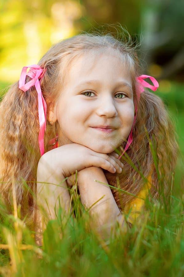 Kleines schönes Mädchen liegt auf grünem Gras, Sonnensommer in Stadt-PA stockfotografie