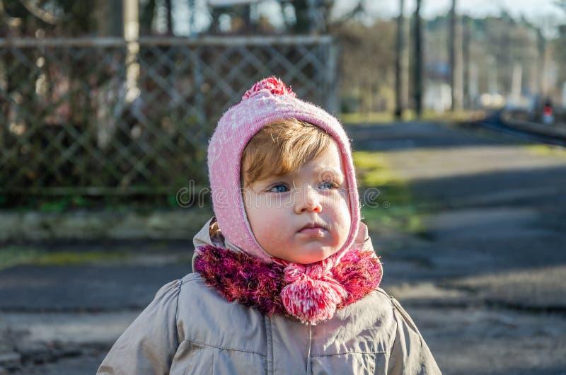Kleines schönes Mädchen mit dem luxuriösen Haarbaby, das auf die Straße an einem sonnigen Tag des Kappen- und Jackenherbstes geht lizenzfreie stockfotografie