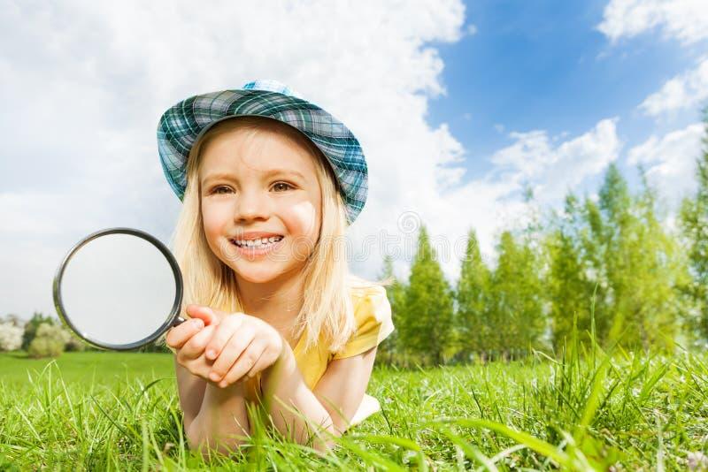 Kleines schönes Mädchen mit dem Vergrößerungsglas, das allein legt stockbild