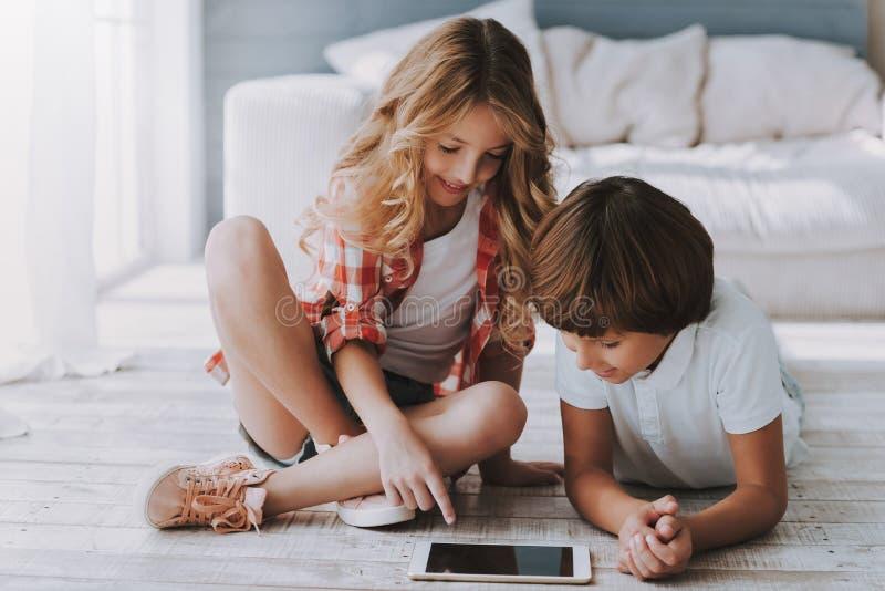 Kleines schönes Mädchen und Junge grasen Internet auf Tablette des Hauses lizenzfreie stockbilder