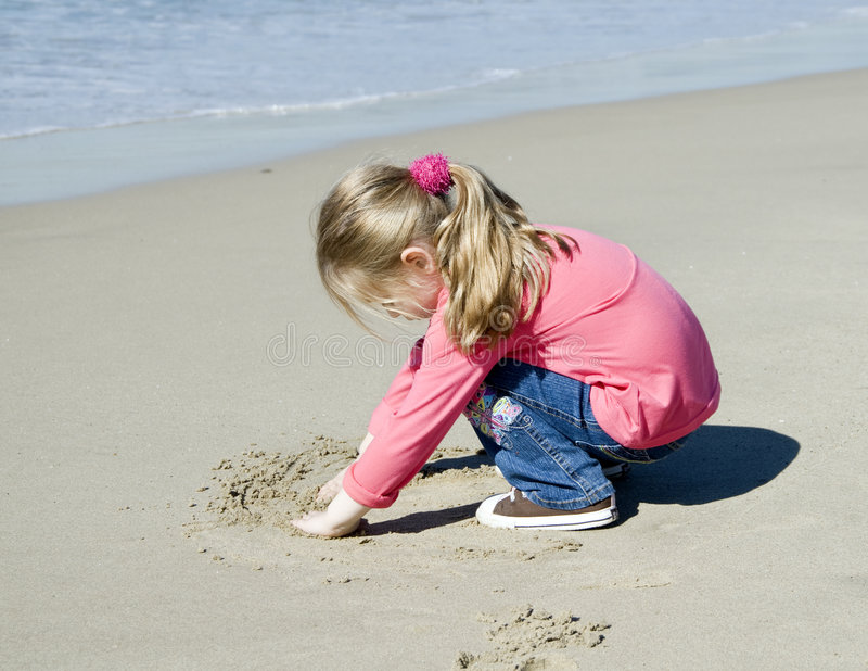 Kleines schönes Mädchen zeichnet auf Sand lizenzfreies stockfoto