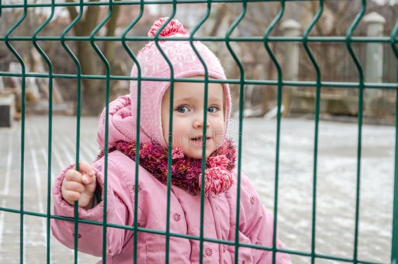 Kleines schönes Mädchenbaby hinter dem Zaun, Gitter schloss in eine Kappe und in eine Jacke mit traurigem Gefühl auf seinem Gesic lizenzfreie stockfotos