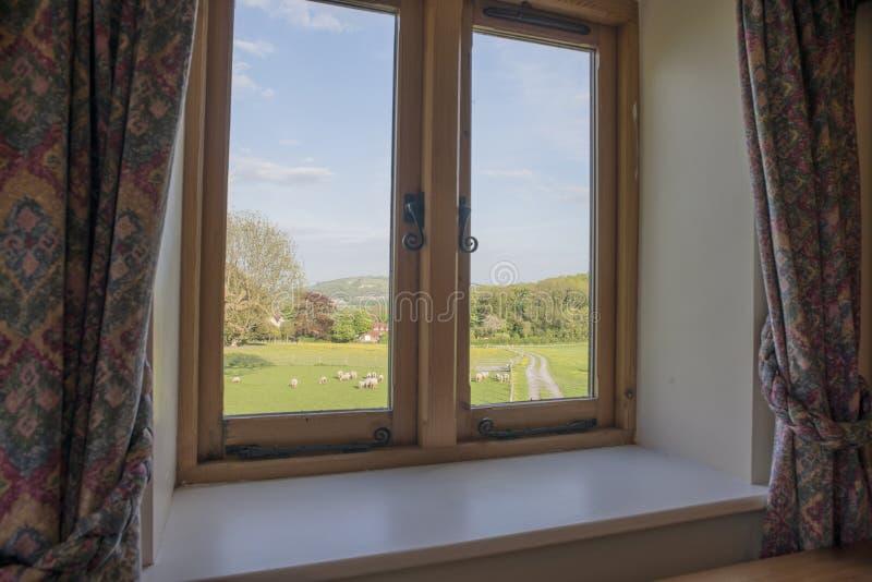 Kleines Schlafzimmer-Fenster mit Ansicht der Bauernhof-und Schaf-Herde stockfoto
