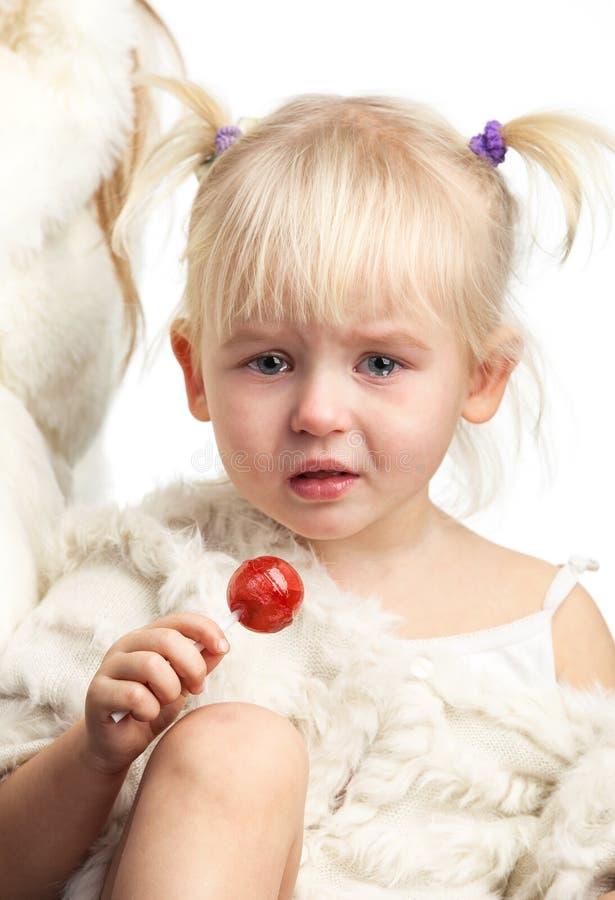 Kleines schreiendes Mädchen mit einer Süßigkeit über Weiß lizenzfreie stockbilder
