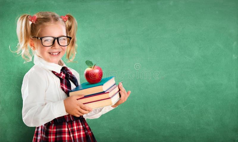 Kleines Schulmädchen, das Bücher hält stockbilder