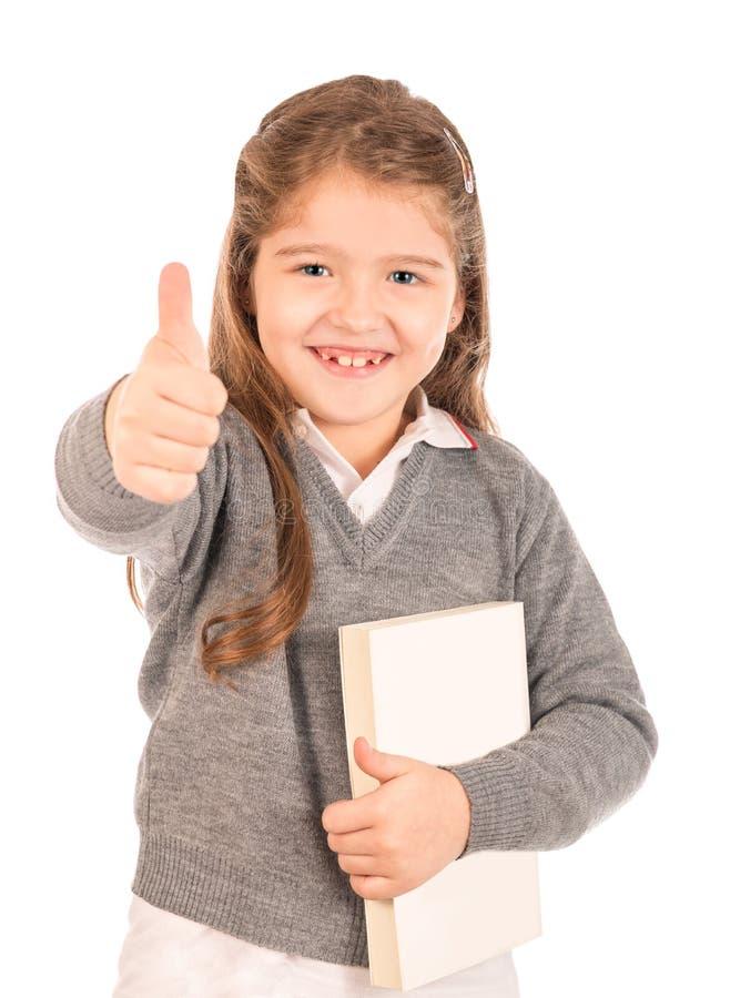 Kleines Schulmädchen, das ein Buchgeben Daumen-oben hält lizenzfreies stockbild
