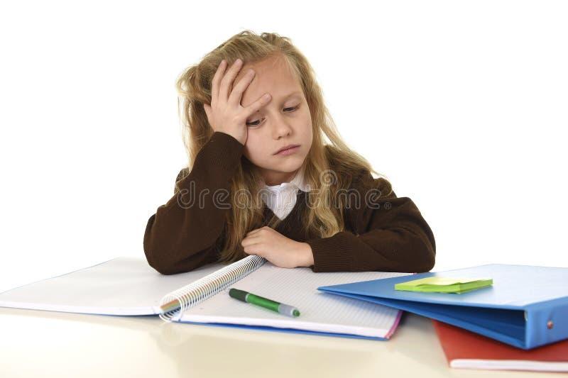 Kleines Schulmädchen traurig und müder schauender niedergedrückter Leidendruck überwältigt durch Last der Hausarbeit lizenzfreie stockbilder