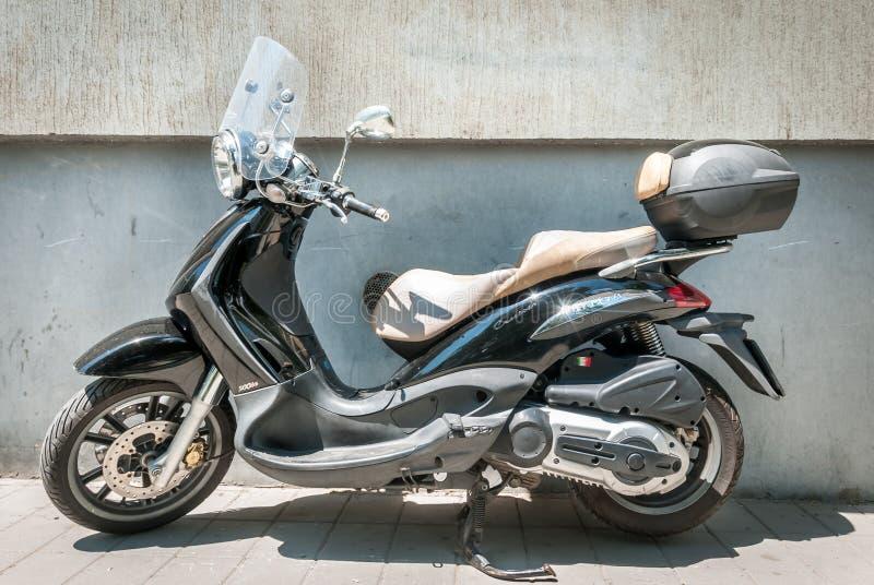 Kleines schwarzes italienisches Rollermotorrad parkte auf der Straße lizenzfreies stockfoto