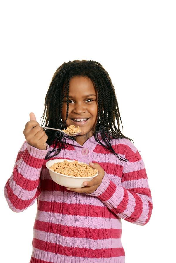 Kleines schwarzes Mädchen, das Schüssel Getreide genießt stockfoto