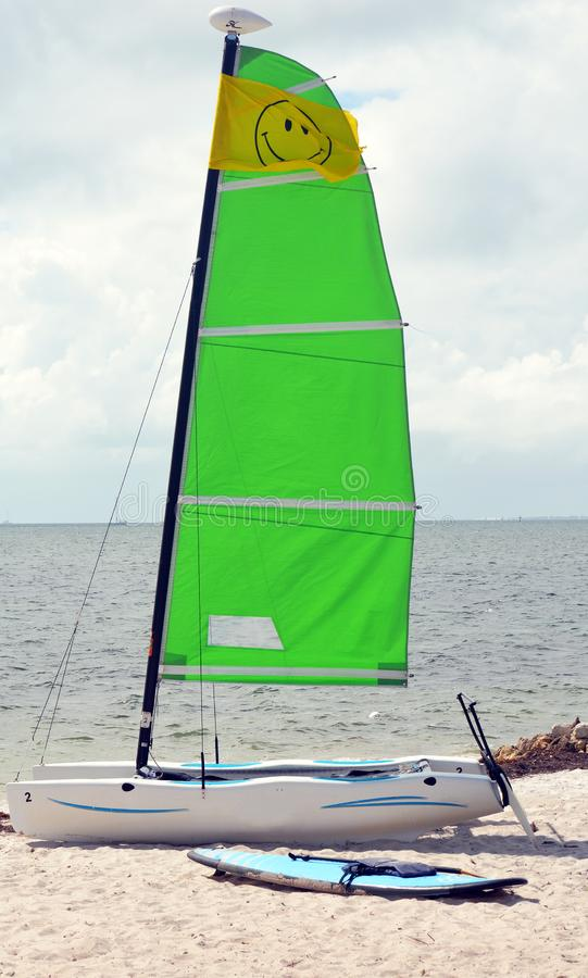 Kleines Segel Katamaran und Paddleboard, die auf einem Florida-Strand stillsteht stockbild