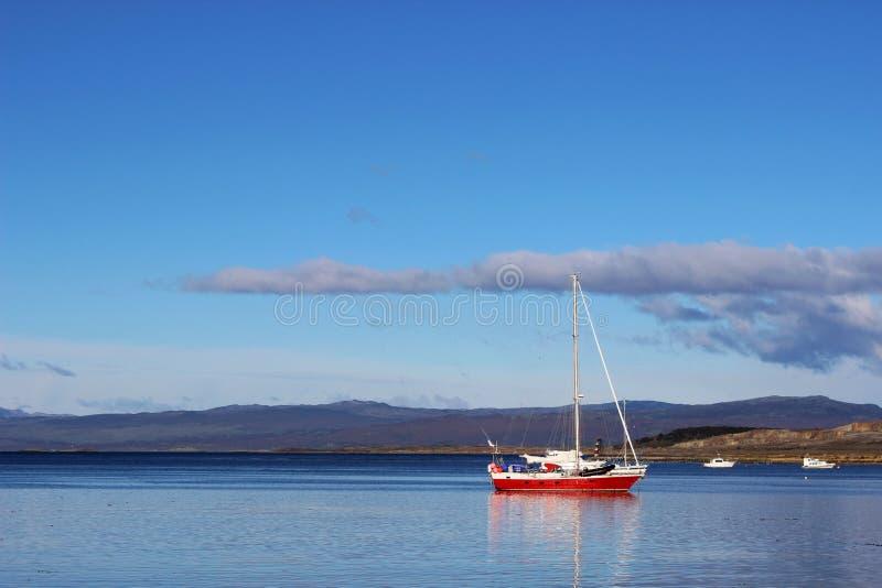 Kleines Segelboot auf ruhigem Wasser lizenzfreie stockbilder