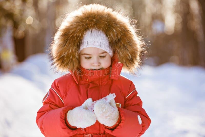 Kleines sehr nettes Mädchen in einer roten Klage mit der Pelzhaube, die icic hält lizenzfreie stockfotos
